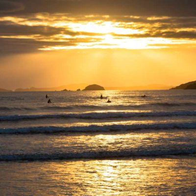 Moody view of surfers sitting in the water with setting sun behind