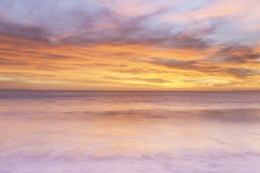 Looking out over a milky sea to an outstanding sunset at Newgale Beach with pinks and orange in the sky