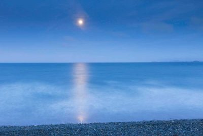 a very simplistic image of the moonlight shining over a dreamy sea at Newgale beach predominantly blues