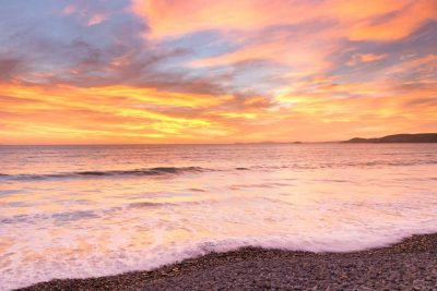 A fiery sunset taken looking north from newgale beach with pebbles in the foreground and a pink, orange and blue welsh coastal sunset