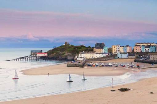 Pink evening skies above Tenby Harbour at low tide with 3 sailing dinghies in the foreground returning from their race