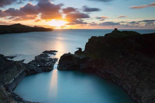 Sunset at the blue lagoon with the sun shining through the gap in the rocks