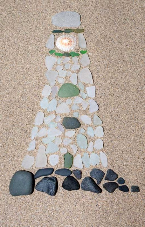 Tall lighthouse made out of predominantly white seaglass with green windows, black rocks and a shell light