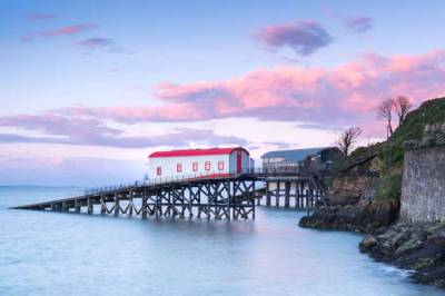 The old lifeboat station at Tenby with pink sunset clouds behind