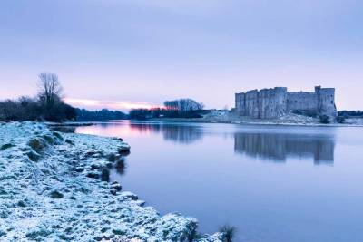 Beautiful frosty morning with a light sprinkling of snow by the millpond at Carew as the sun rises behind the castle