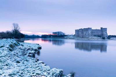 A calm morning at Carew tidal mill with snow on the ground and the pink glow of a rising sun