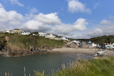 looking back on Little Haven from half way up the point with fluffy clouds and blue skies