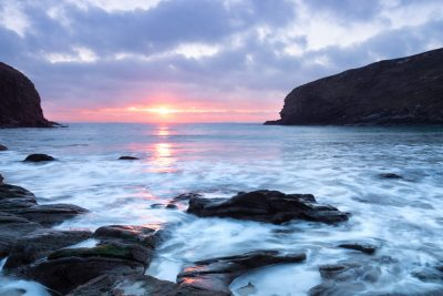 pink sunset at nolton haven with pink sunbeam across sea going on to rocks with milky water washing over them