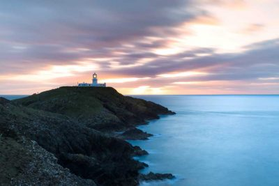 A Dreaming pink and purple sunset behind Strumble Head lighthouse
