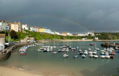 A rainbow over the houses of north beach with Tenby Harbour in the foreground