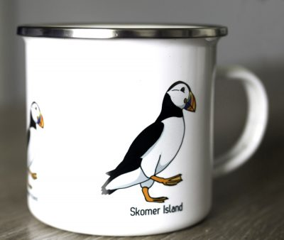 bright white enamel mug with 3 graphic design puffins and the words Skomer Island