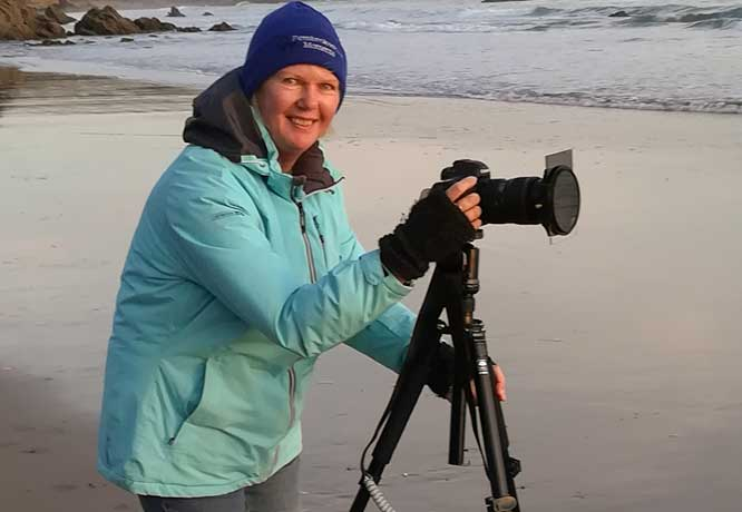 Rachel Mullett with her camera on a tripod on a cold winter Pembrokeshire sunset taking photographs