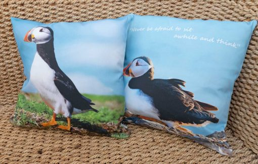 beautiful panama cotton cushion with polyester filler with two images of skomer puffins on either side, one sitting, one standing