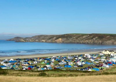 Looking down on the campsite at Newgale packed full of tents and vans on a busy bank holiday and out to sea at Newgale