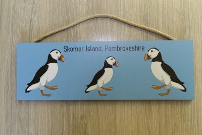 three puffins drawn from one of my photographs against a blue background on a large hangingplaque