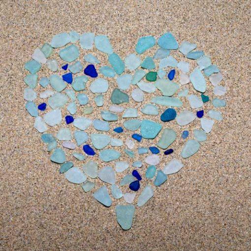 Beautiful blue and aqua blue seaglass forming a heart on a sand background