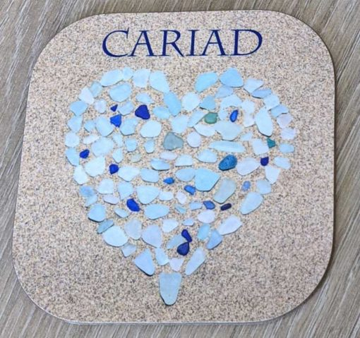 seaglass heart made of pale turquoise and blue glass with the word Cariad above it built on sand