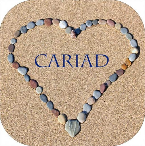 Pebble heart on sand with the word Cariad in the centre on a high gloss coaster