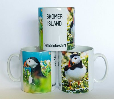 ceramic mug with 2 photographs of puffins in flowers and the words Skomer Island, Pembrokeshire