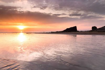 A dramatic orange sunset at low tide at Broad Haven North