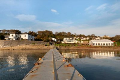 View from the end of the pontoon at Burtoon looking back to the Jolly Sailor Pub and old Trinity House property in the golden light of evening with a blue sky