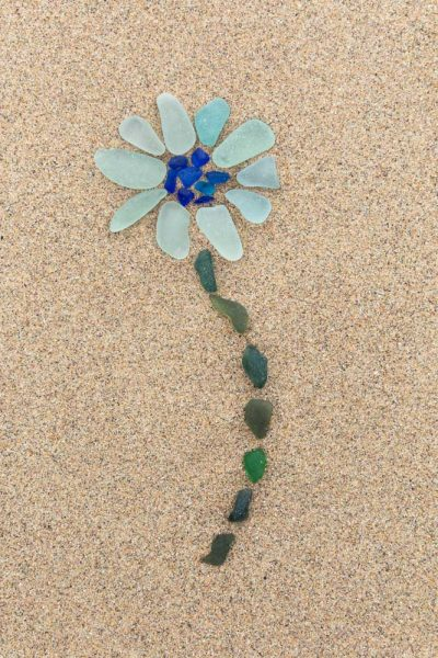 A pale blue seaglass flower with a dark blue centre and green stem on Pembrokeshire sand base