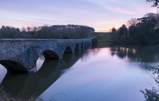 a pink purple glow with the eight arch bridge leading to the sun just beginning to peep out over the fields at stackpole