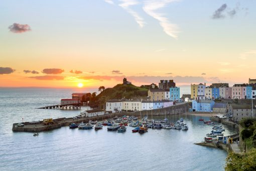 a winter sunrise with the sun rising behind the lifeboat stations looking down on Tenby harbour