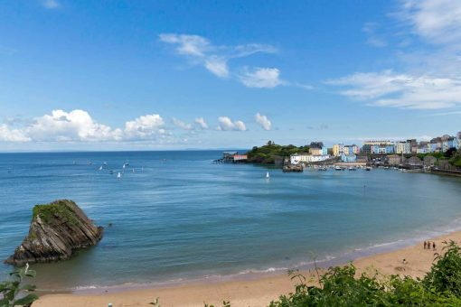 View across North Beach Tenby with Goscar Rock and sailing boats to Tenby Harbour