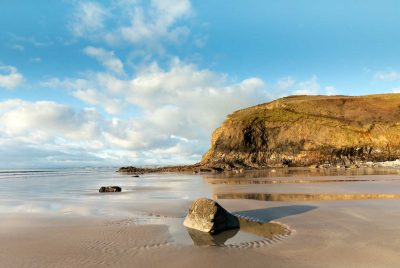 Light turquoise sky with white fluffy clouds drawn out by a wide angle lens looking north on druidstone beach with a rockpool in foreground and cliff reflections in the wet sand