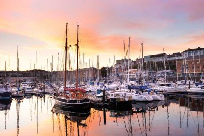 dramatic orange and blue skies as a backdrop for the boats at Milford Marina Wales