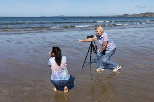 Rachel teaching a student camera skills on Newgale Beach at a Pembrokeshire Photography Workshop