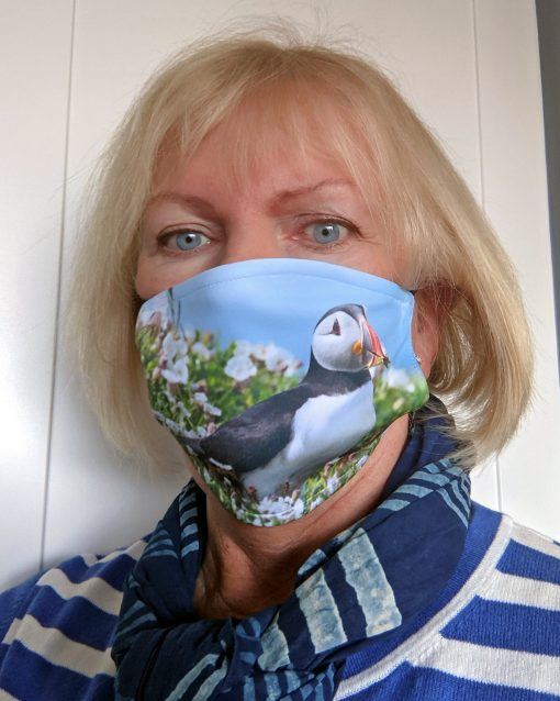 rachel of pembrokeshire moments is modelling her new face masks with a puffin in white campion