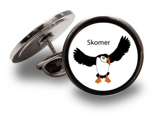 a graphic design puffin coming in to land with the word Skomer above on a silver coloured lapel pin
