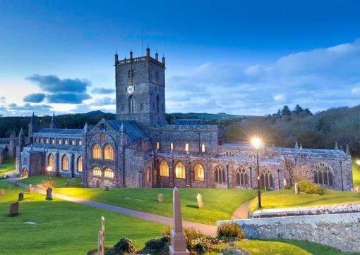 St Davids Cathedral with the lights on as day turns to twilight with blue darkening skies
