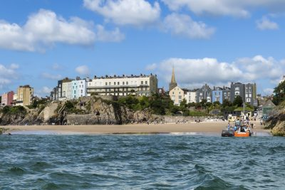 this image was taken looking back at tenby castle beach from a trip boat going to caldey island. there's sea, sand and beautiful clifftop houses along with the dennis cafe on the beach