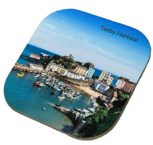 looking down on tenby harbour with the boats and coloured houses and bright blue sea and sky