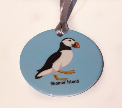 beautiful high gloss ceramic circular hanging charm with a graphic art design of a puffin against a pale blue background