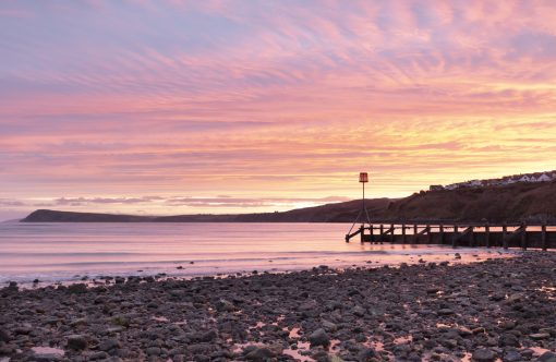 a pink and orange sunrise over fishguard to Dinas head taken from the shore at Goodwick