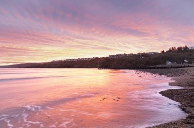 milky waves on goodwick foreshore with red seas and skies looking towards fishguard at sunrise