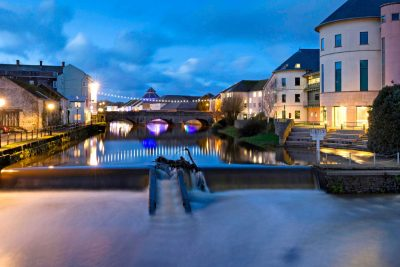 photograph taken from a bridge looking at the weir upstream in haverfordwest at twilight time