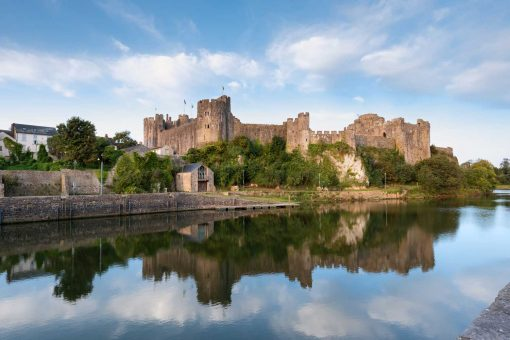 still waters reflecting the blue skies and light clouds with pembroke castle as the main feature