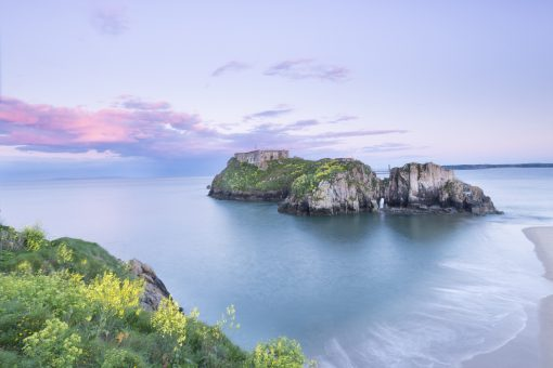 looking towards st catherines island with pale pink clouds and a purple glow surrounding it at high tide in tenby