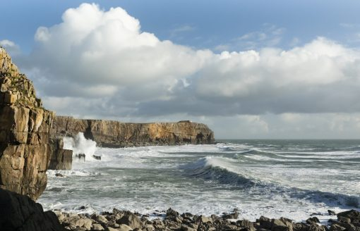 sunshine and fluffy clouds above a stormy sea with waves crashing on to rocks at St Govans Head