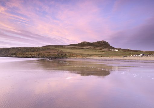 pink sunset skies above Carn Llidi with the wet sand in the foreground reflecting the beautiful colours of the sky