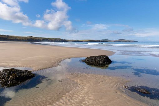a beautiful sunny day standing on whitesands beach at low tide with rockpools in the foreground looking across the beach looking south towards ramsey island