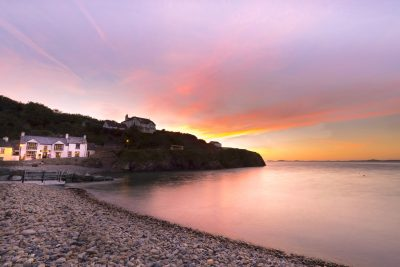 pink, purple and orange skies reflecting over a milky sea looking towards the swan inn at little haven