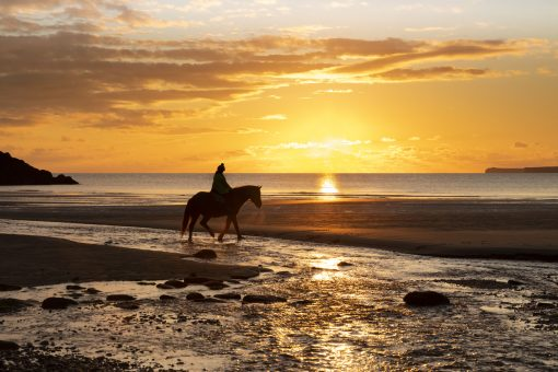 an orange sunset at manorbier beach with a horse and rider crossing the image to make a lovely pembrokeshire silhouette